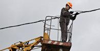 Сотрудник коммунальной службы восстанавливает линию электропередач. Архивное фото