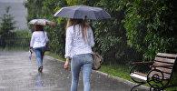 Женщины идут по улице во время дождя. Архивное фото