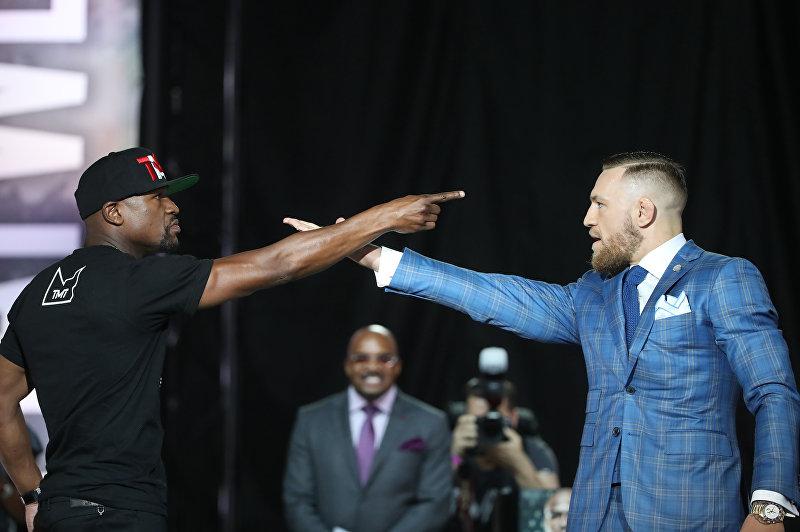 Экс-чемпион мира по боксу в пяти весовых категориях американец Флойд Мейвезер-младший и чемпион UFC в легком весе ирландец Конор Макгрегор во время пресс-конференции в Торонто (Канада)