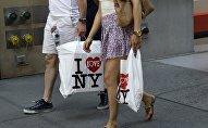 Муж и жена с пакетами выходят из торгового цента. Архивное фото