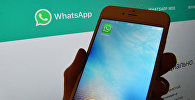 Иконка мессенджера WhatsApp на экране смартфона и веб-страница на экране компьютера. Архивное фото