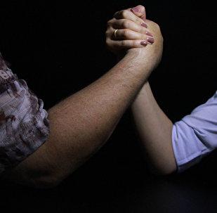 Мужчина и женщина соревнуются по армрестлингу. Архивное фото