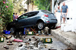 Люди проходят мимо поврежденного автомобиля, после мощного землетрясения в Эгейском море у побережья Турции