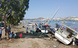 Люди стоят рядом с поврежденными лодками, после мощного землетрясения в Эгейском море у побережья Турции