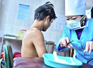 Медсестра делает перевязку пациенту. Архивное фото