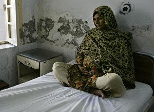 Беременная женщина ждет врача в родильном отделении районной больницы Музаффаргарха в провинции Пенджаб, Пакистан