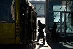 Автобуска түшүп жаткан адамдын архивдик сүрөтү