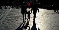 Муж и жена с ребенком гуляют по парку. Архивное фото