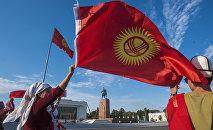 Люди с национальным флагом на площади Ала-Тоо в Бишкеке. Архивное фото