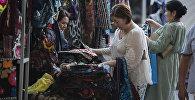 Женщины выбирают одежду на выставке. Архивное фото