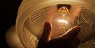 Мужчина выкручивает лампочку от светильника. Архивное фото