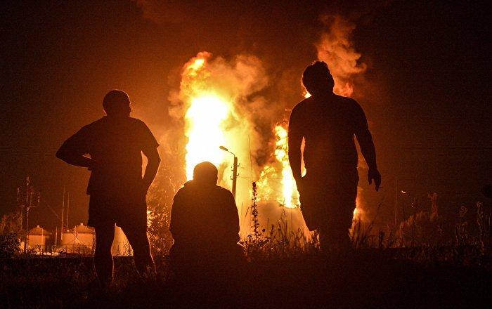 Силуэты мужчин у горящего здания. Архивное фото