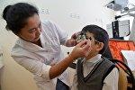 Окулист-педиатр во время осмотра ребенка. Архивное фото