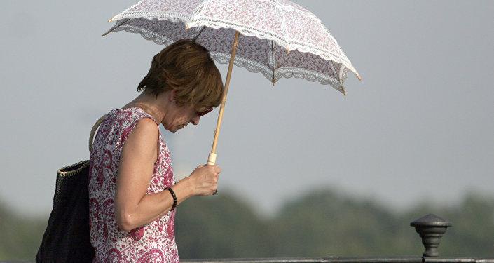 Женщина укрывается от жары под зонтиком. Архивное фото