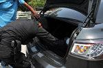 Полицейский проверяет багажник автомобиля. Архивное фото