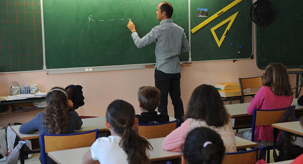 Учитель пишет на доске во время урока в школе. Архивное фото