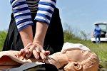 Девушка проходит практическое занятие на манекене по оказанию первой помощи. Архивное фото