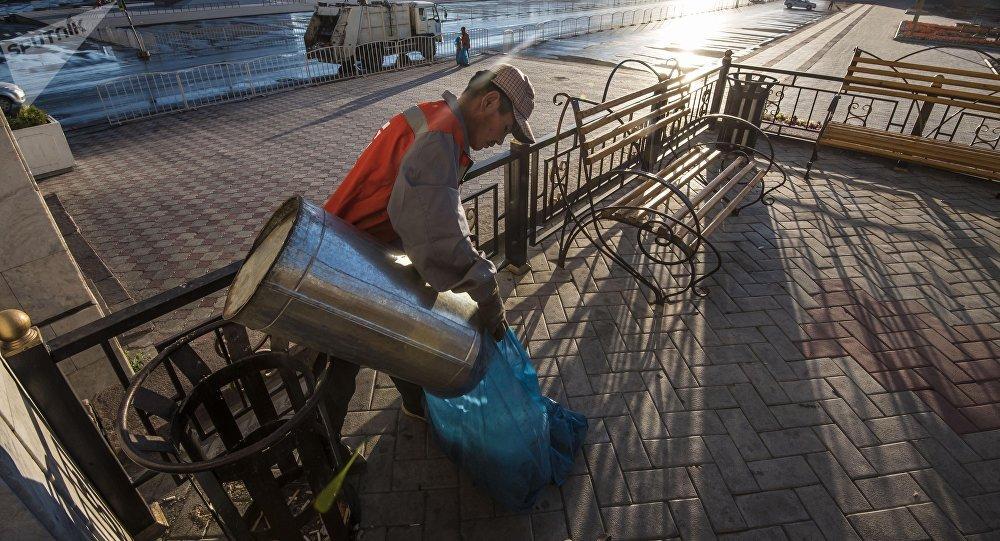 Работник муниципального предприятия Тазалык во время уборки мусора на площади Ала-Тоо в Бишкеке. Архивное фото