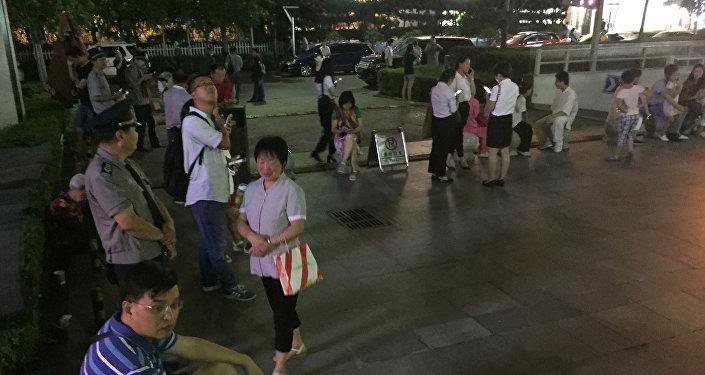 Люди стоят на улице после землетрясения в китайской провинции Сычуань. 8 августа 2017 года