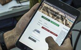 Мужчина держит планшет с открытым сайтом evisa.e-gov.kg, где можно оформить электронную визу в КР