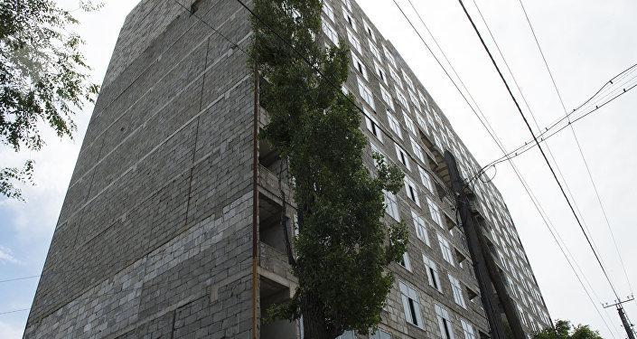 Строящийся 12-этажный дом по улице Суюмбаева, часть стены которой обрушилась из-за ветра
