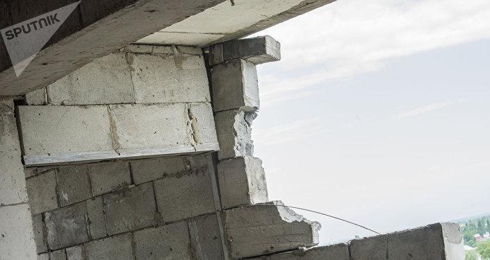 Сильный ветер, вероятно, стал причиной обрушения части стены строящегося 12-этажного дома по улице Суюмбаева