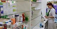 Сотрудница аптеки разбирает лекарства. Архивное фото