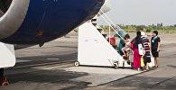 Пассажиры захолят в самолет в международном аэропорту в селе Тамчи. Архивное фото