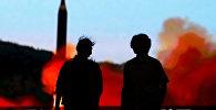 Люди смотрят за запуском ракеты в КНДР. Архивное фото