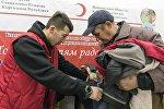Сотрудник Красного креста в Бишкеке помогает нуждающемуся