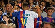 Мальчик жестом показывает в майке с аргентинским форвардом Лионеля Месси в Барселоне и нападающим португальского форварда Реала Криштиану Роналду. Архивное фото