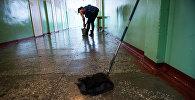 Уборщица моет пол в одной из школ. Архивное фото