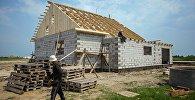 Рабочие на строительстве дома. Архивное фото