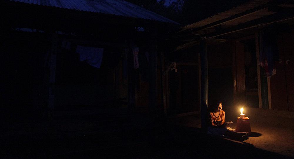 Молодая девушка читает книгу у свечки. Архивное фото