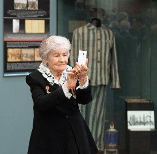 Бабушка фотографирует на камеру мобильного телефона. Архивное фото