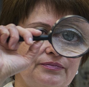 Женщина смотрит в лупу. Архивное фото