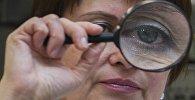 Женщина смотрит через лупу. Архивное фото