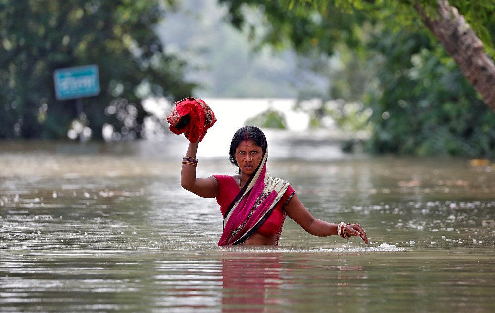 Индиянын Бихар штатында аял суу каптаган көчөдө кетип бара жатат. Андагы жаратылыш кырсыгынан каза болгондордун саны 253кө жетти.
