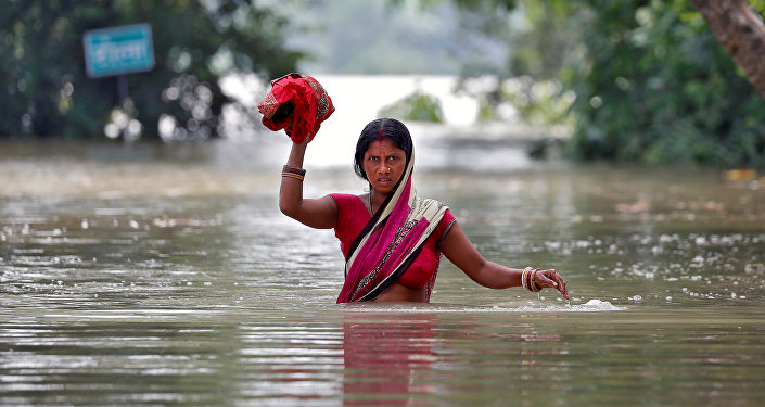 Женщина идет по затопленной улице в одном из деревень индийского штата Бихар. Число погибших в результате наводнений на востоке страны возросло до 253 человек