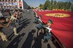 Военнослужащие с флагом КР на площади Ала-Тоо в Бишкеке во время празднования 26-летия независимости Кыргызстана