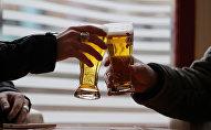 Двое мужчин пьют пиво за барным столом. Архивное фото