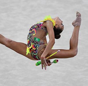 Российская спортсменка Дина Аверина выполняет упражнения с булавами в финальных соревнованиях на чемпионате мира по художественной гимнастике в итальянском Пезаро