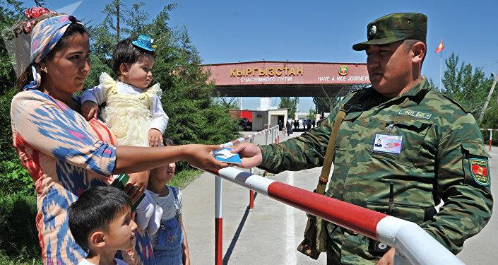 Пограничник КР проверяет паспорт на контрольно-пропускном пункте кыргызско-узбекской границы в Кара-Суу на юге Кыргызстана. Архивное фото