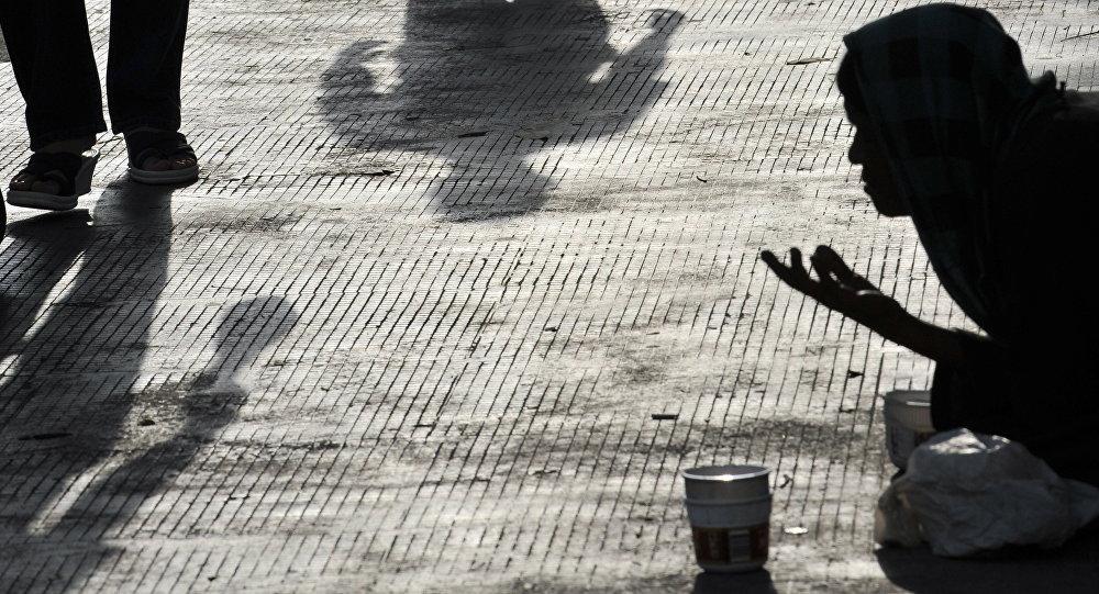 Нищий просит милостыну на пешеходной дороге. Архивное фото