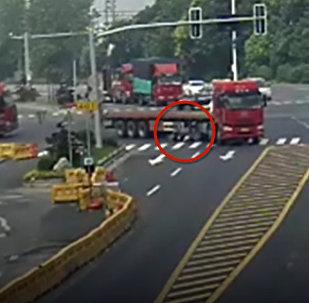 Грузовик наехал на женщину, она чудом осталась жива — видео из Китая