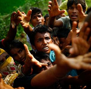 Беженцы-рохинджа протягивают руки за едой во время раздачи еды во временном лагере города Кокс-Базар, Бангладеш