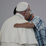 Бийликтин аскерлери менен болгон кармашта колунан айрылган колумбиялык тургун Рим папасы Францискти кучактап турат