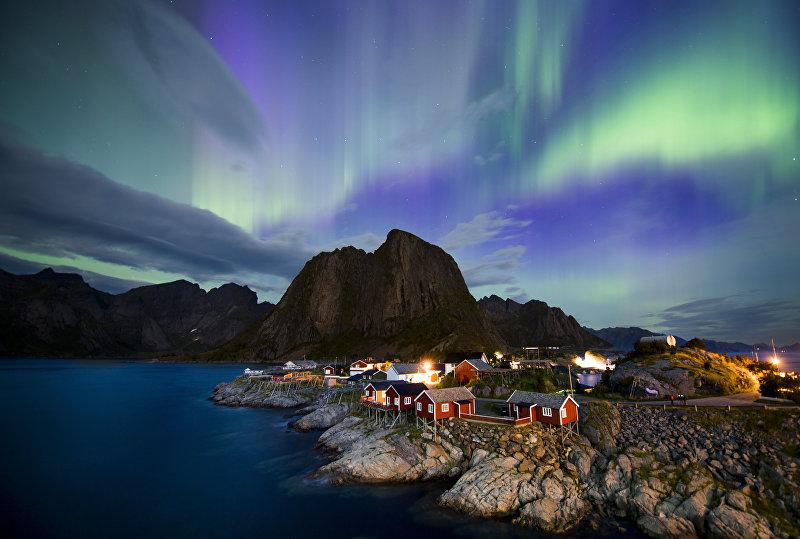 Северное сияние освещает небо над Лофотенскими островами, в Норвежском море у северо-западного побережья Норвегии