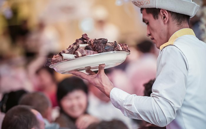 Официант с тарелкой полного мяса на одном из свадеб в Бишкеке. Архивное фото