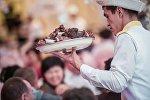 Официант с тарелкой полного мяса на одном из свадеб в Бишкеке
